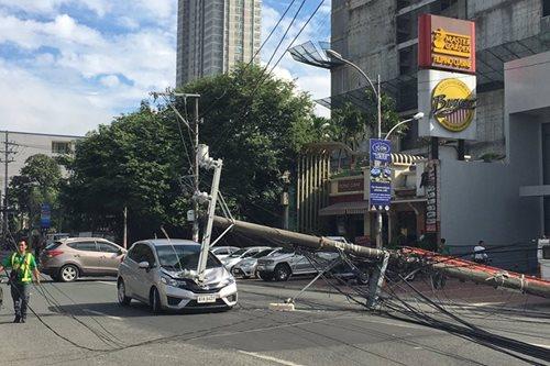 Electric post falls in QC, hits passing car