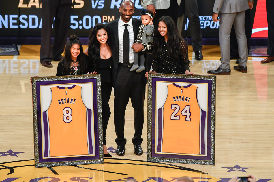 893490ae6 Former Lakers player Kobe Bryant (C) and family pose for a photo during a  halftime ceremony to retire the two uniform at Staples Center.