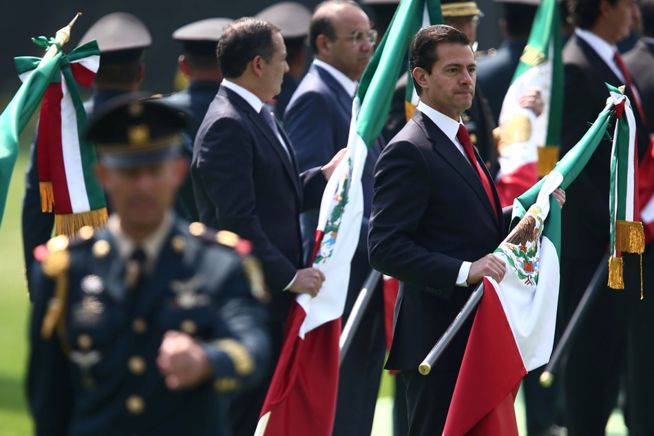 Mexico's President Enrique Pena Nieto holds a Mexican flag during Flag Day celebrations in Mexico Saturday. Edgard Garrido Reuters