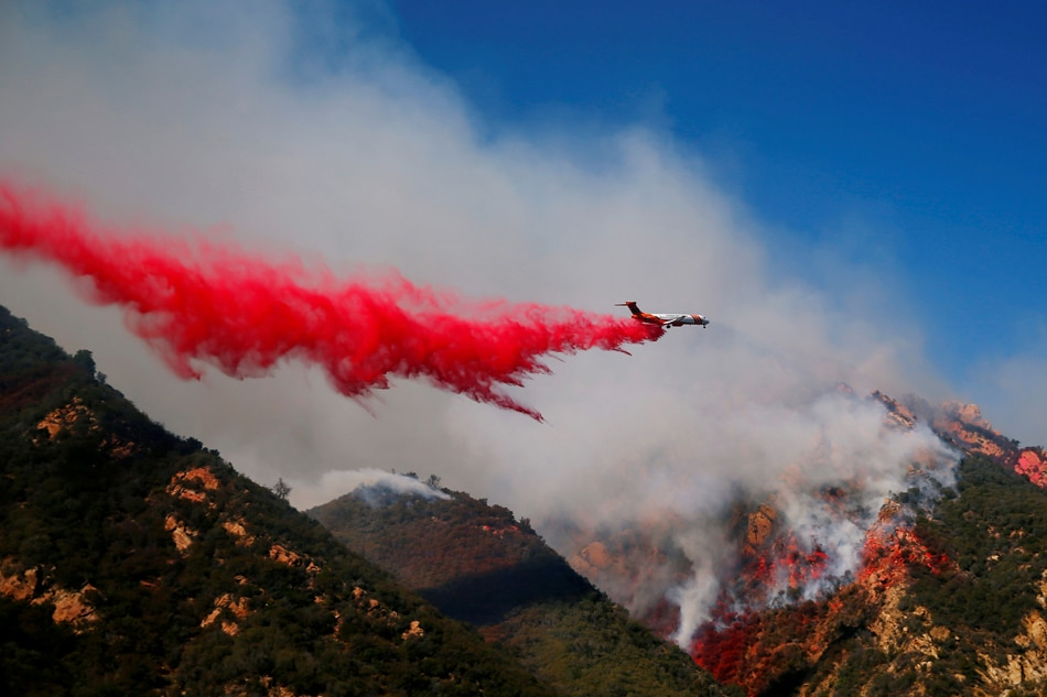An aircraft drops flame retardant as firefighters battle the Woolsey Fire as it continues to burn in Malibu. Reuters