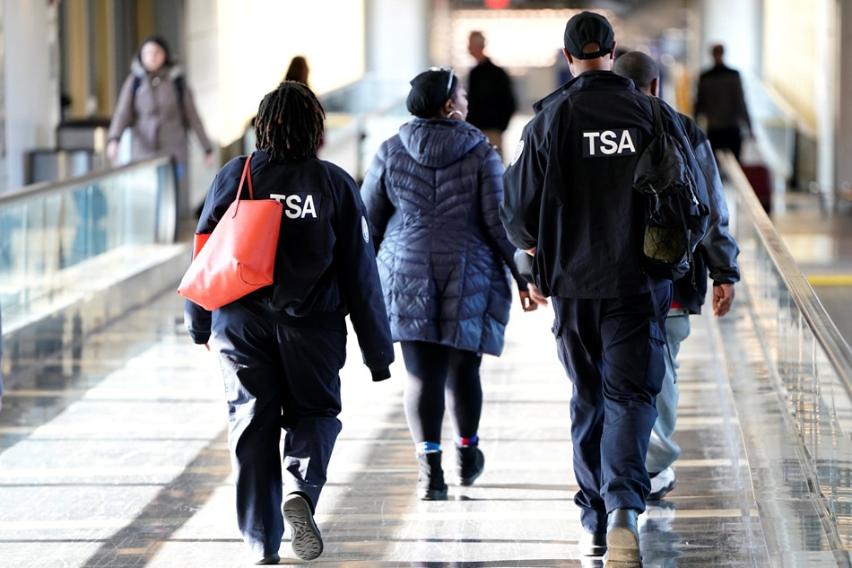 Employees with the Transportation Security Administration walk through Reagan National Airport in Washington. Reuters