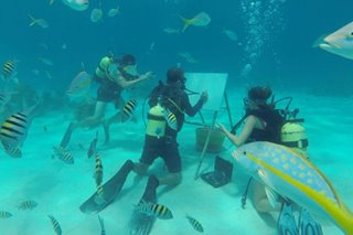 Artist sketches under the sea among fish and coral reefs