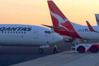 Passengers evacuate Qantas plane via emergency slides at Sydney airport