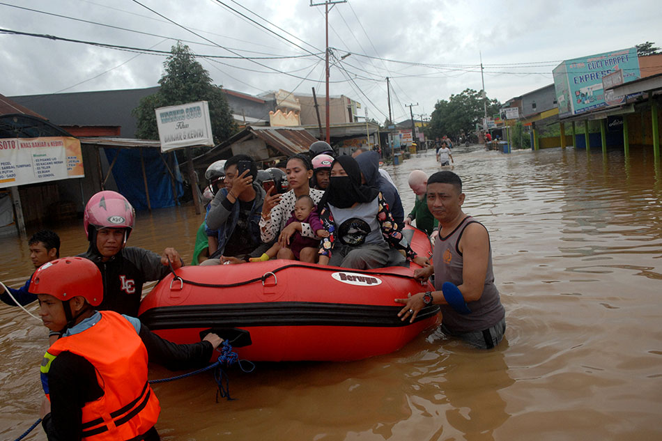 Rescue workers push an inflatable boat as they evacuate residents following floods in Makassar, South Sulawesi, Indonesia, January 23, 2019 in this photo taken by Antara Foto.