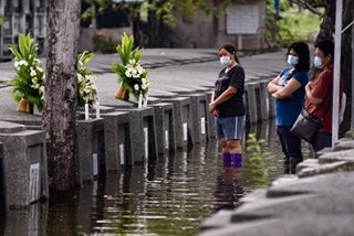 LOOK: Despite floods, relatives visit loved ones in Pampanga cemetery