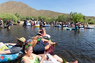 Crowds pack Arizona river as US posts record COVID-19 cases for 3 days running