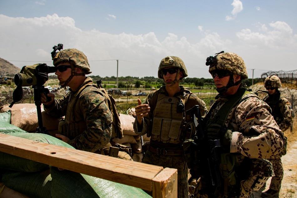 US Marines and German service member watch an entry gate during an evacuation at Hamid Karzai International Airport, Kabul, Afghanistan, August 28, 2021. U.S. Marine Corps/Cpl. Davis Harris/Handout via Reuters