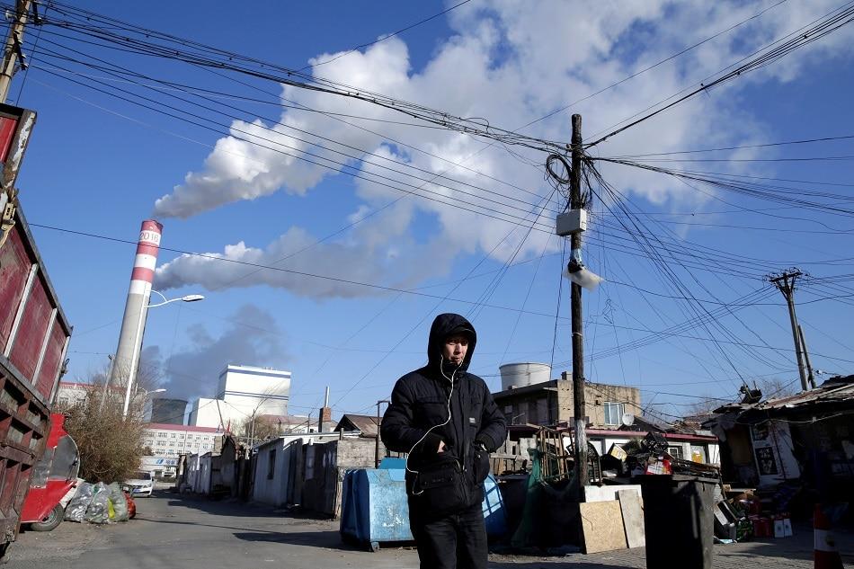 A man walks near a coal-fired power plant in Harbin, Heilongjiang province, China November 27, 2019. Picture taken November 27, 2019. Jason Lee, Reuters/file